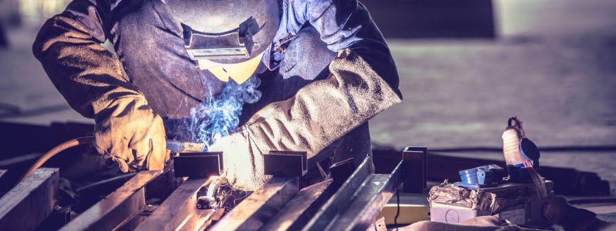 Factory worker hand welding steel