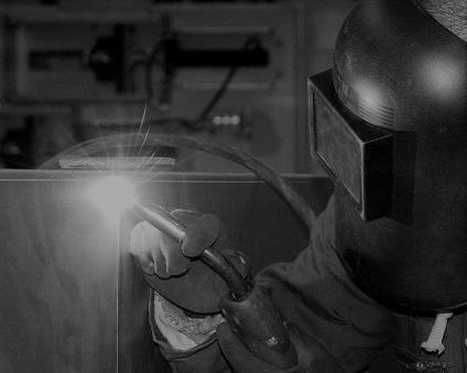 Factory worker welding steel