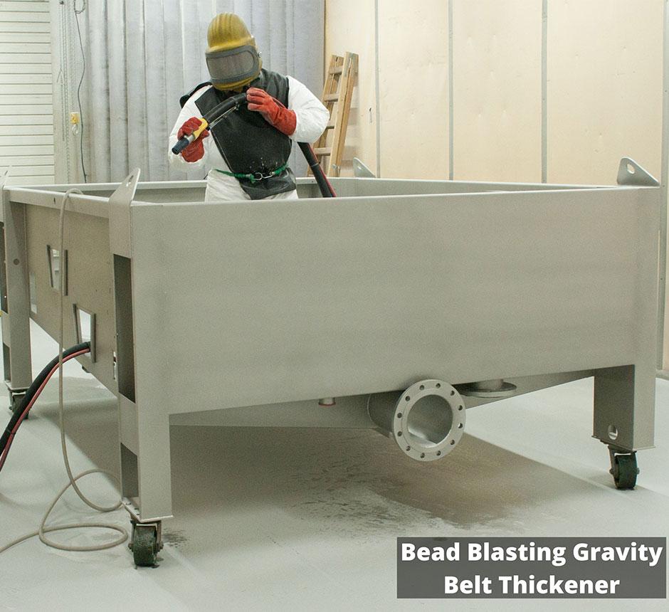 Factory worker Bead Blasting a Gravity Belt Thickner